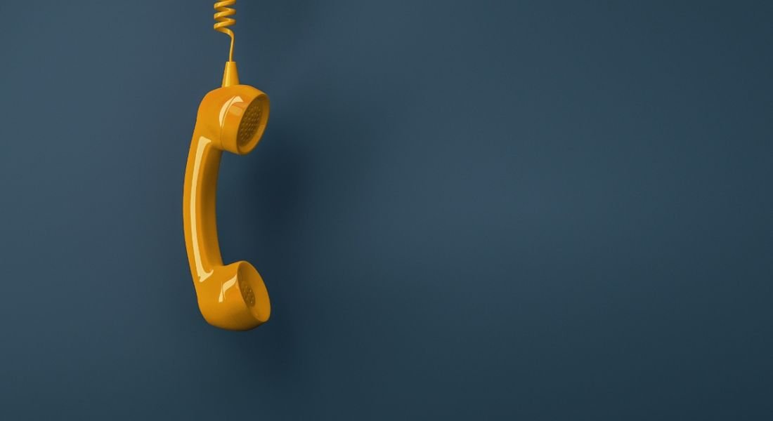 Shot of a yellow landline telephone receiver against a dark background.
