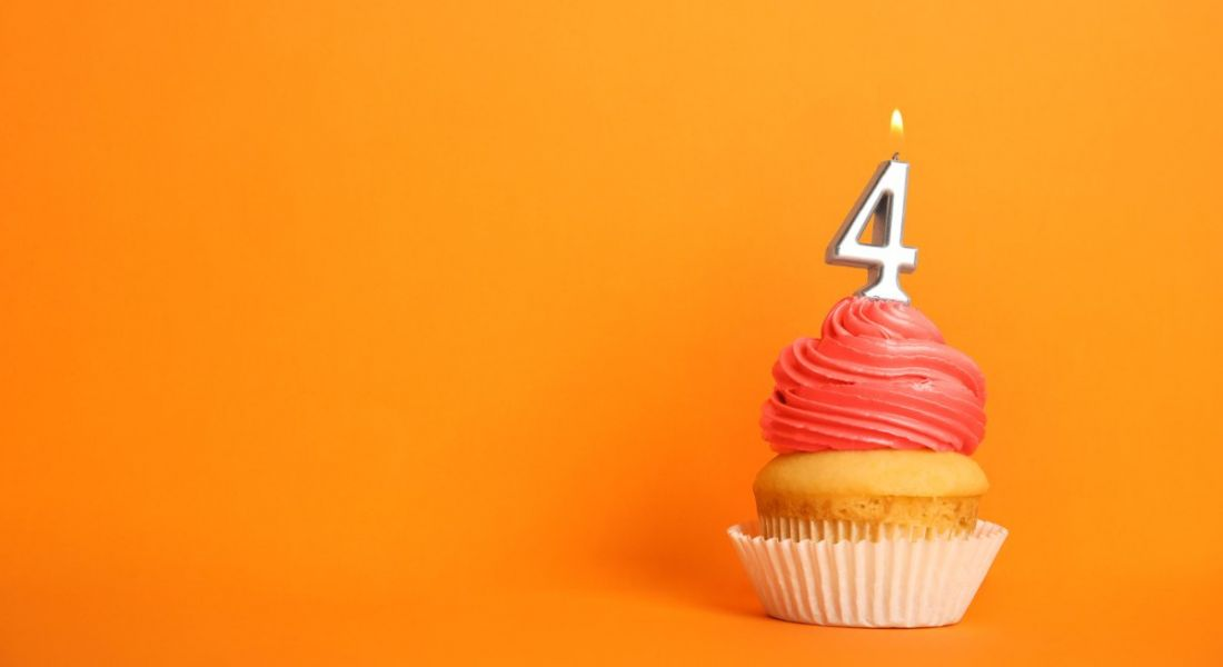 Birthday cupcake with number four candle against an orange background.
