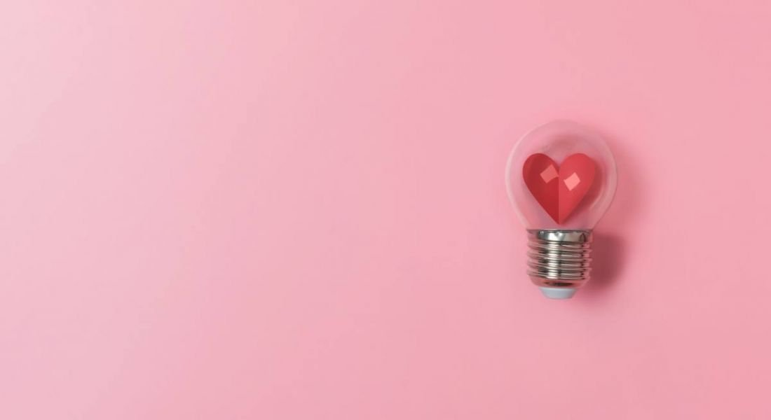 Red heart in light bulb on pink background, representing mental health and wellbeing.