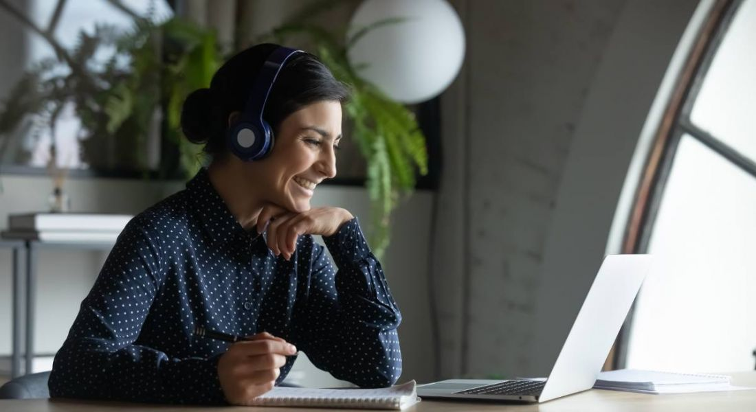 A woman is taking part in virtual training on her laptop at home.