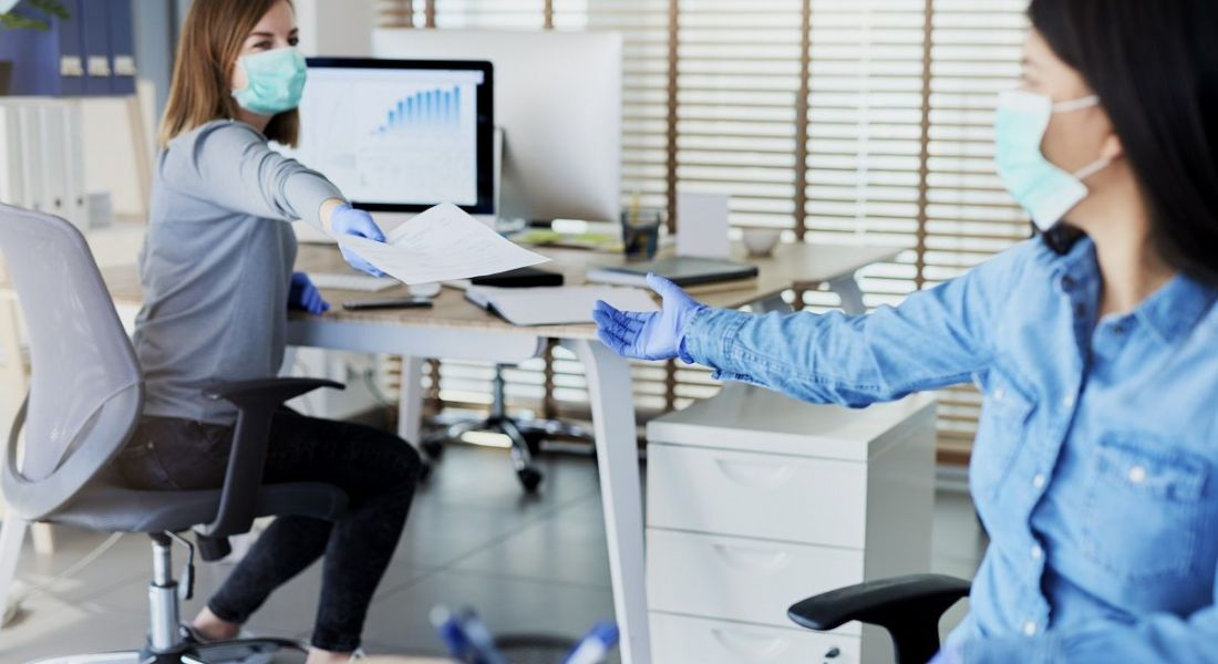Two people in an office passing documents while wearing face masks and keeping a distance from each other.