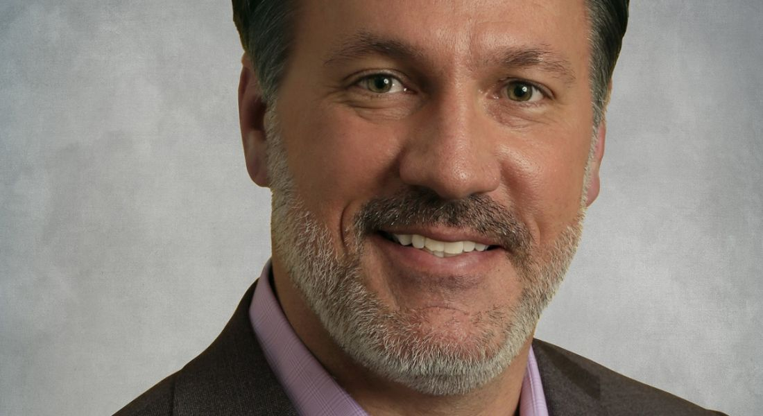 Chris Huff of Kofax is smiling into the camera in front of a grey background.