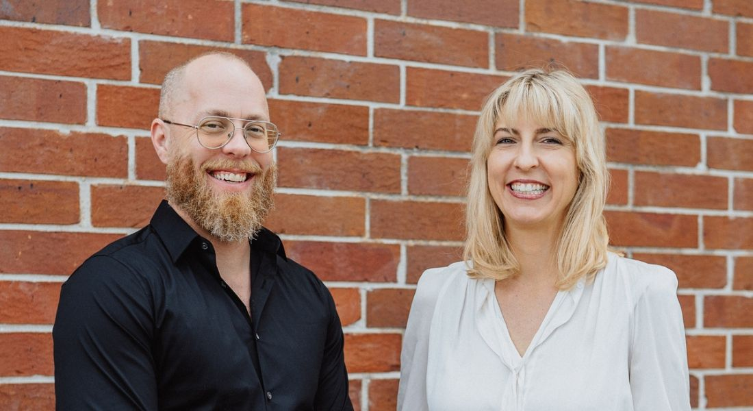 Douglas Ferguson and Karen Holst are standing against a red-brick wall and smiling into the camera.