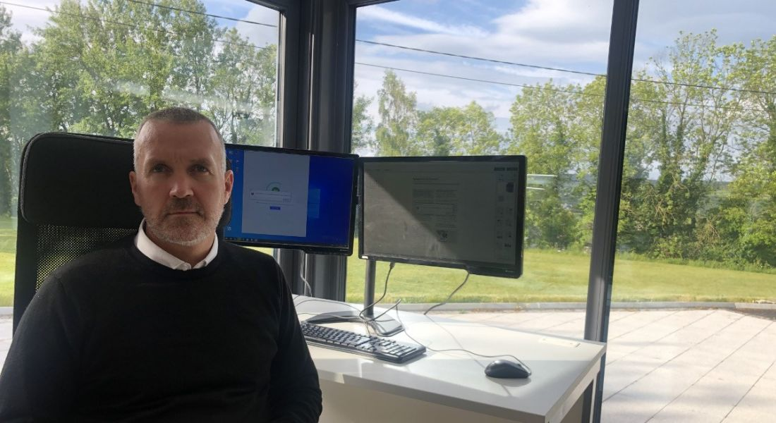 Paul McNulty of 3D Issue is sitting at home by a large window and a desk with monitors on it.