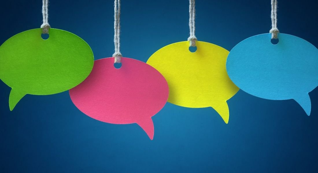 Four different coloured paper speech bubbles hanging by string against a dark blue background, symbolising conversations.