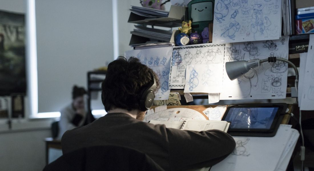 An animation student is working at a station in IADT, surrounded by sketches.