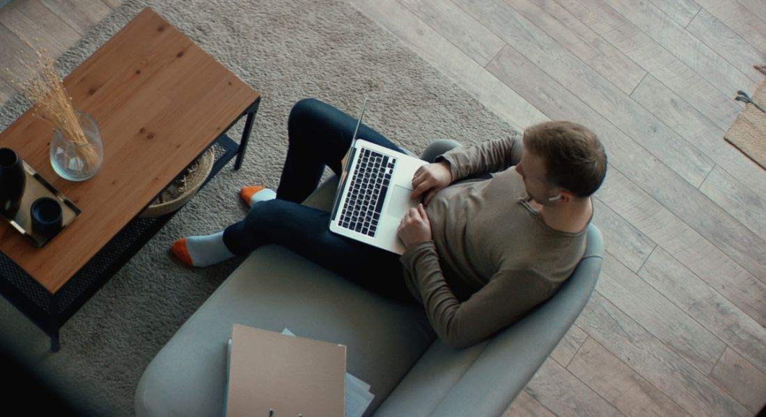 An aerial view of a man remote-working on a laptop on his couch.