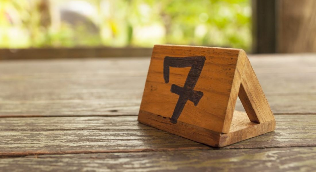 A wooden table sign with the number seven on it sits on a wooden table against a backdrop of greenery.