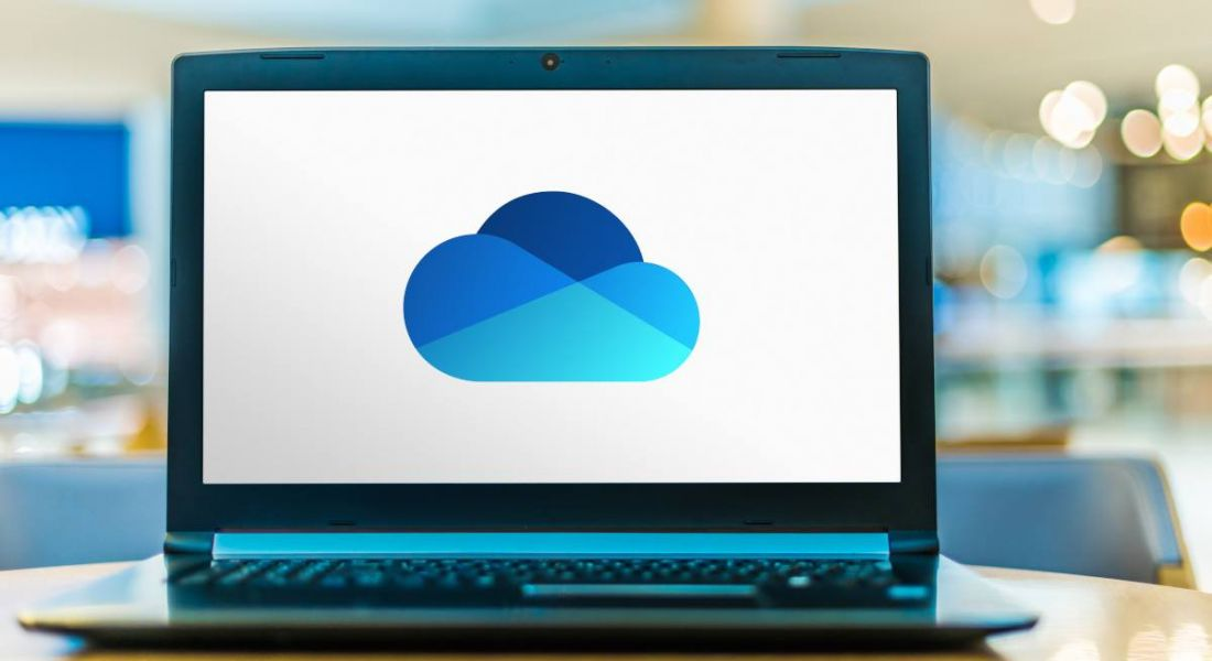 A laptop computer is displaying the blue cloud-shaped logo of Microsoft One Drive.