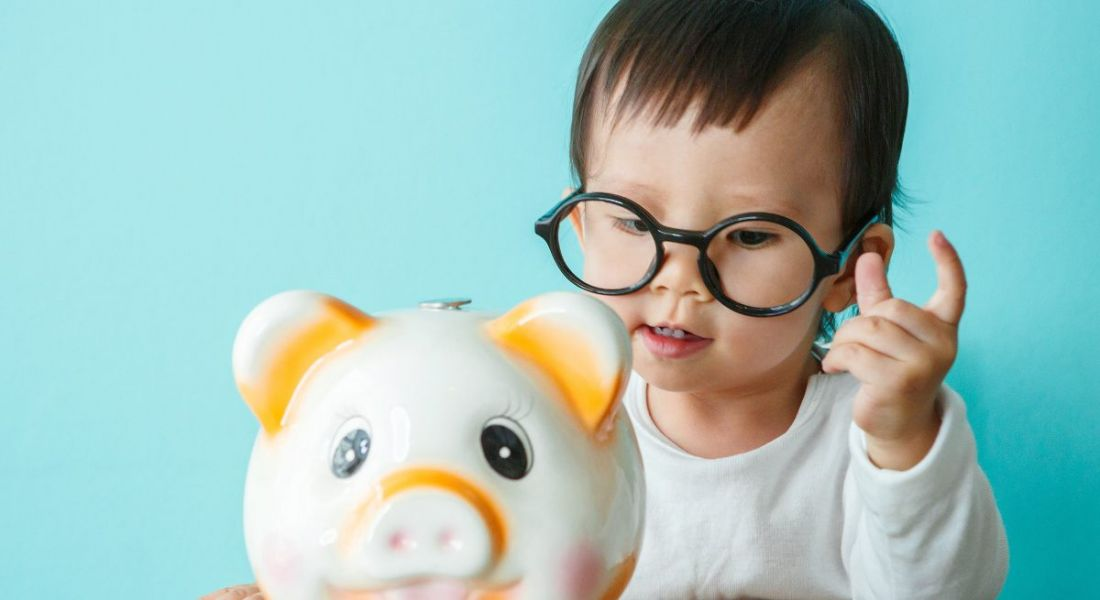 A baby wearing glasses putting a coin in a white and orange piggy bank.
