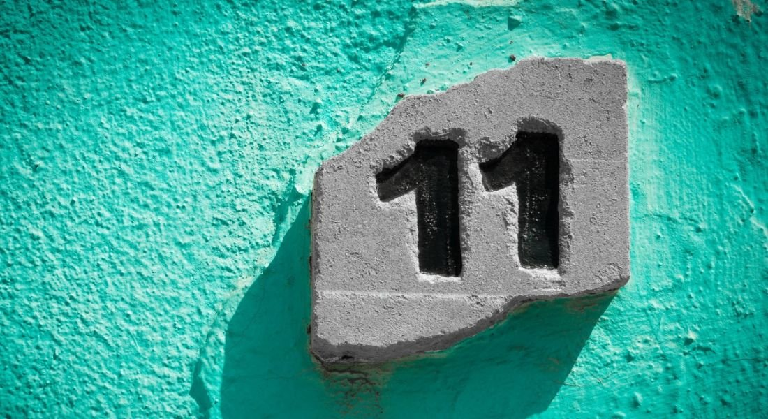 The number eleven engraved on a stone, which is placed against a teal stone wall.