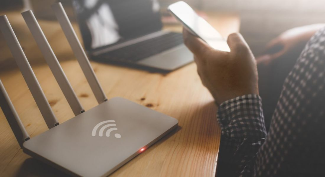 Close-up of a wireless router and a person using a smartphone at home.