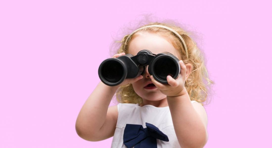 A small child is looking through binoculars on a pink background.