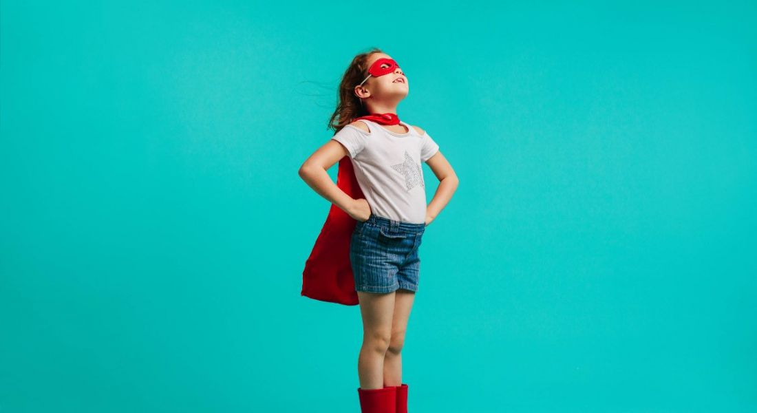 A young girl is dressed up as a superhero against a blue background, symbolising self-confidence.