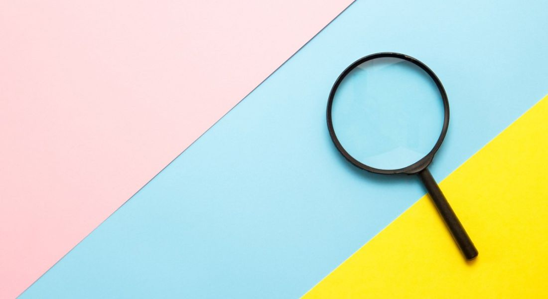 A black magnifying glass is lying against a colourful background of pastel yellow, blue and pink.