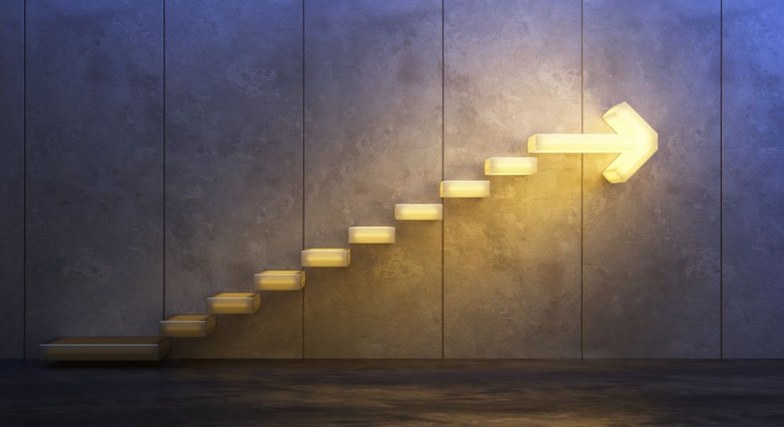 Lit up steps are leading to a bright arrow against a dark wall, symbolising moving onwards and upwards.