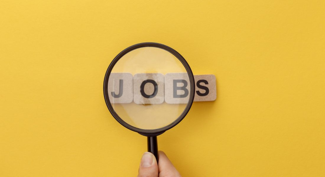 A hand is holding a magnifying glass over wooden blocks spelling out the word 'jobs' against a yellow background.
