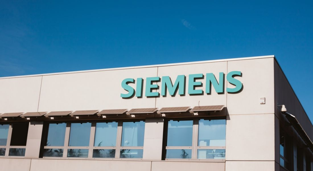 Siemens company logo on a grey building against a bright blue sky.