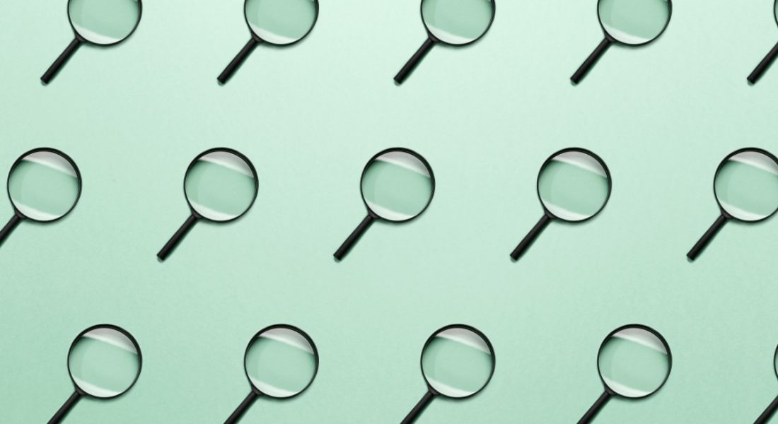 Small magnifying glasses are lined up against a mint-green background, symbolising job searches.