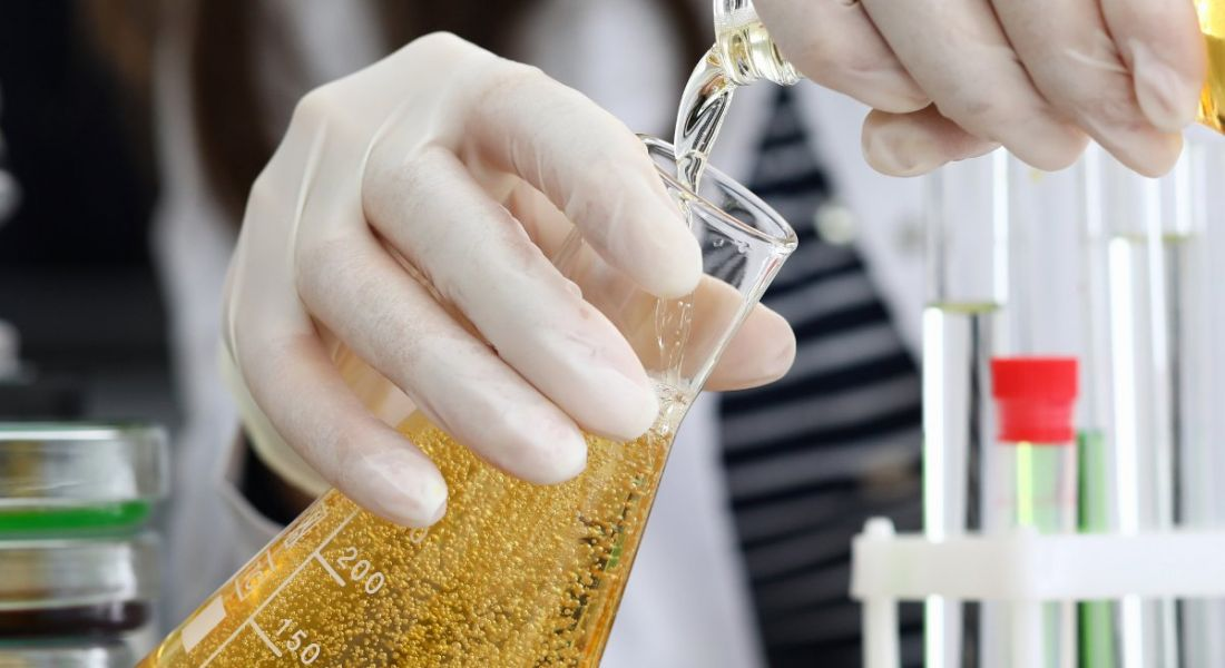 Close-up of a person's hands pouring chemicals in a lab.
