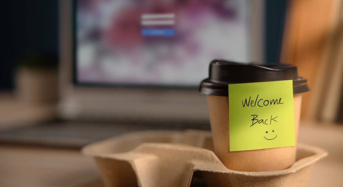 A cup of coffee is sitting on an office desk welcoming an employee back to work.