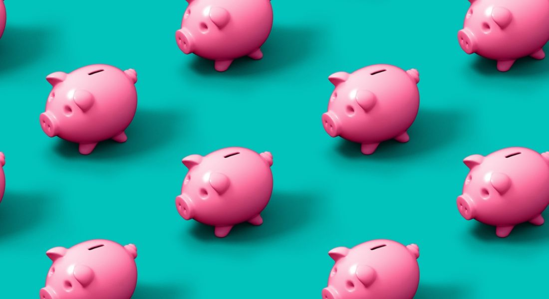 Bright pink piggy banks are sitting against a turquoise background.