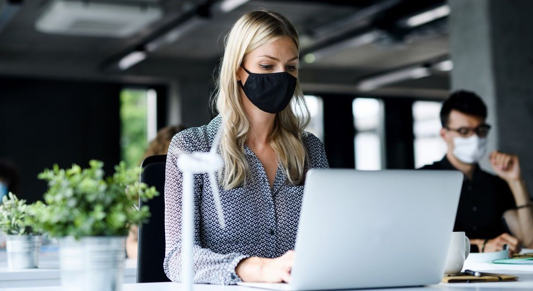 Woman wearing a face mask in an office at a laptop at a distance from someone else wearing a face mask.