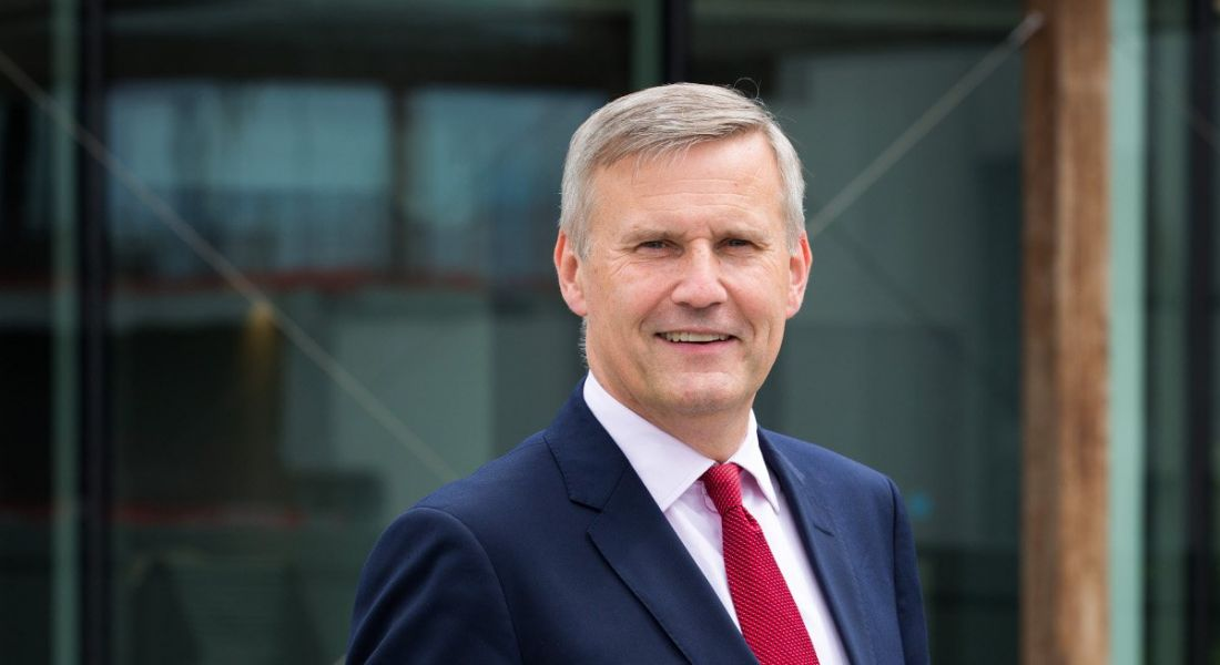 Alastair Blair of Accenture is wearing a suit and red tie and standing outside while smiling into the camera.