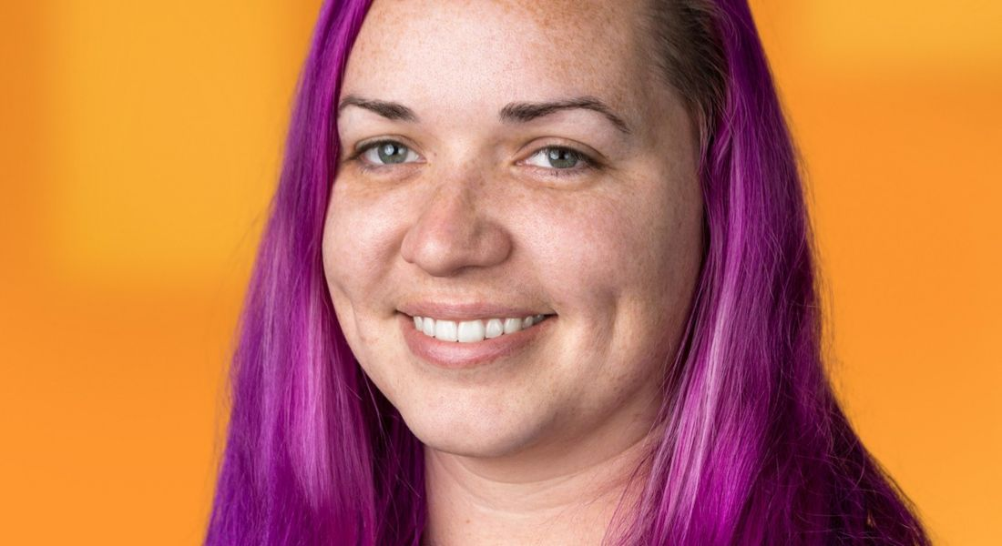 Chrystal Taylor, a head geek at SolarWinds, is smiling into the camera against a bright orange background.