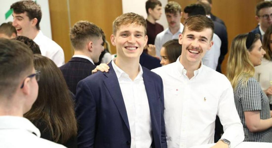 Rob Muldowney and Paddy Ryder, founders of Covid Interns, are standing at an event and smiling into the camera.