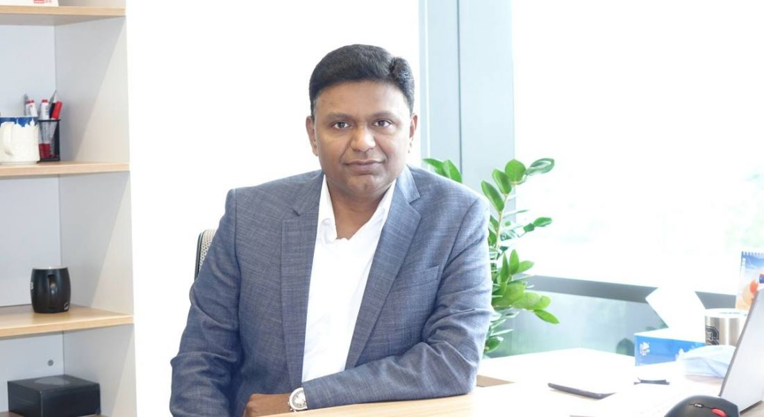 Sanjeev Menon of Lenovo is sitting in an office and smiling into the camera.