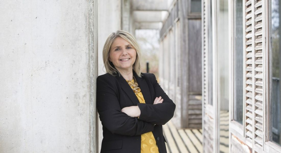 Prof Sarah Culloty is standing against a wall in UCC with her arms folded while smiling into the camera.