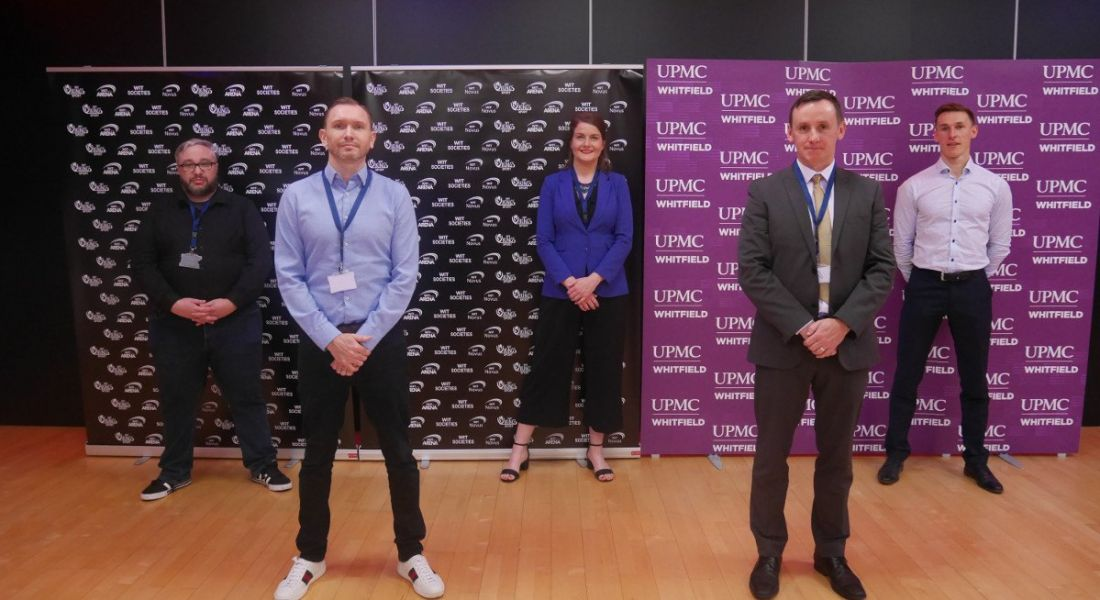 The team behind the new e-sports scholarship at Waterford IT is standing in a sports hall and smiling into the camera.