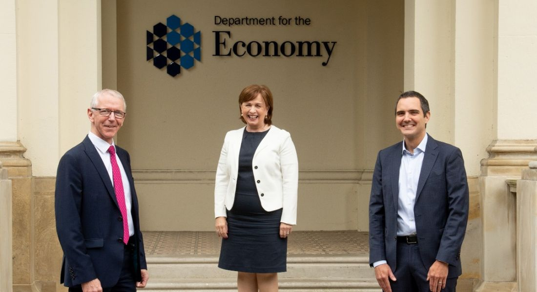 Two men and a woman in business attire stand outside the Department of the Economy in Northern Ireland.