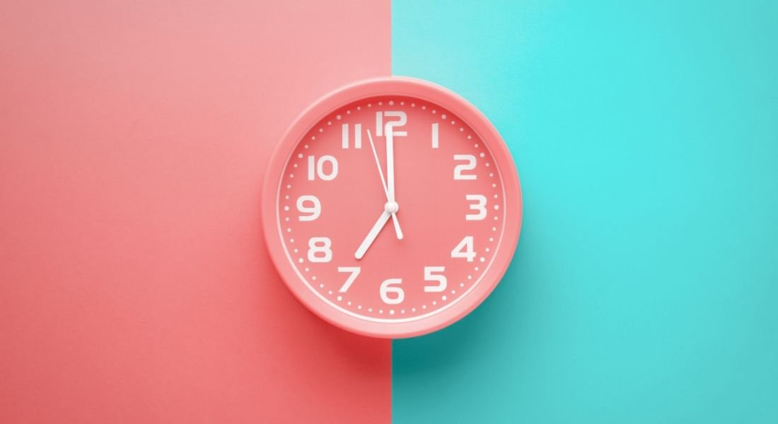A graphic image of a pink clock set against a pink and blue background.