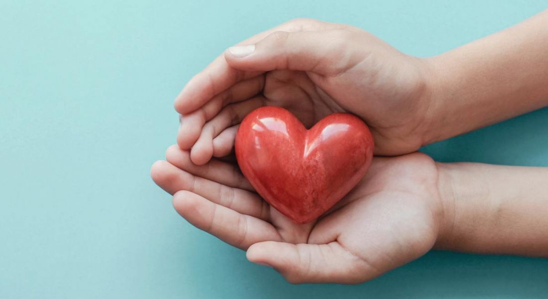 A pair of hands holding a red, wooden heart against a bright blue background.