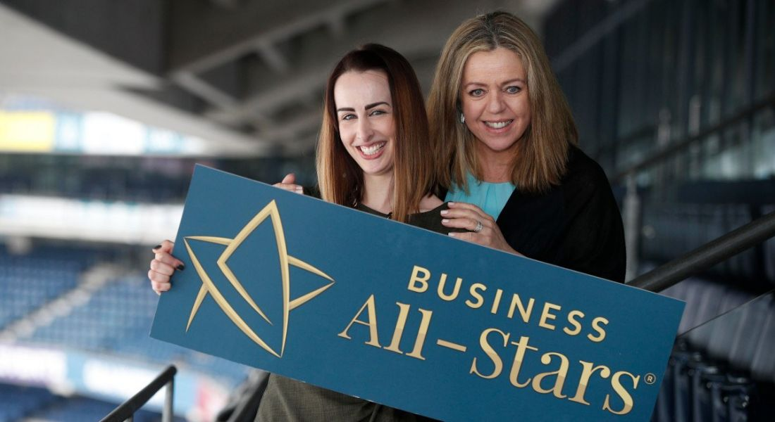 Fiona Descoteaux and Annabelle Conway stand in stadium stalls holding a banner that says Business All-Stars.