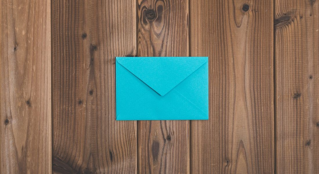A bright blue envelope on a wooden background, symbolising a resignation letter.