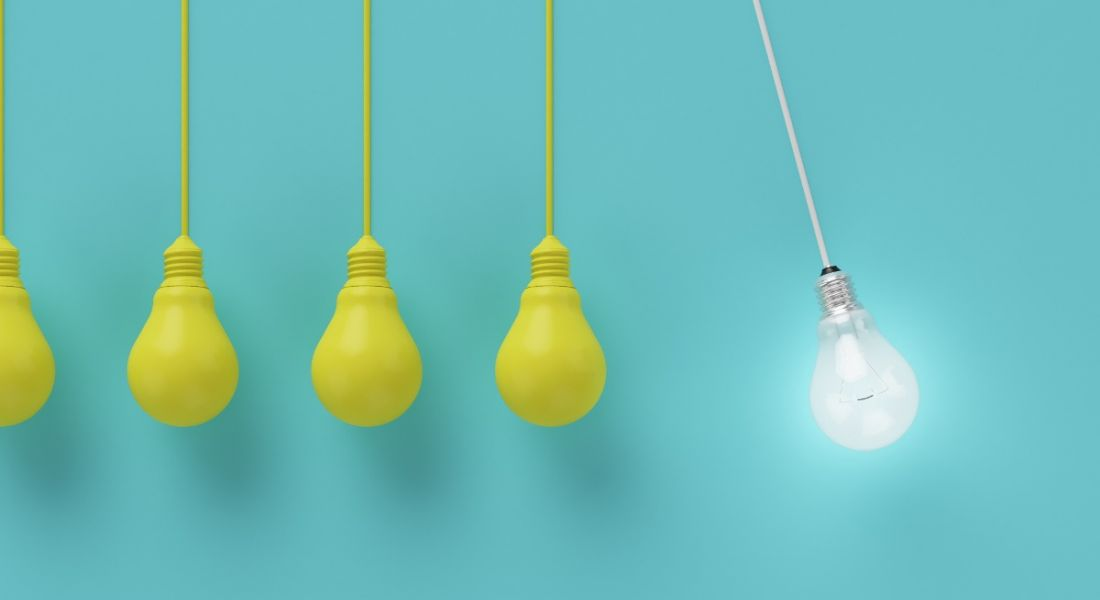 Five yellow lightbulbs hanging against a blue background, with one white lightbulb shining brightly beside them.