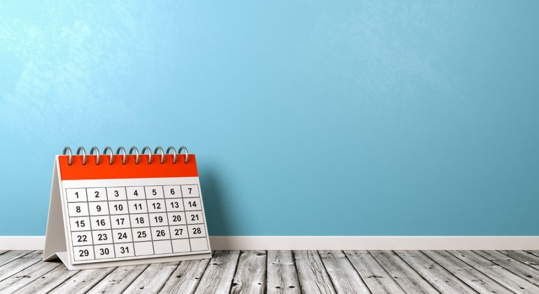 A calendar is sitting on a grey wooden floor against a painted blue wall.