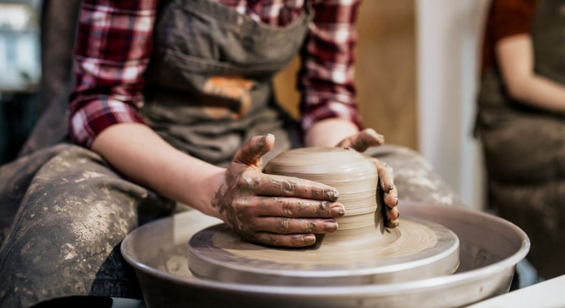A potter is making clay pottery on a spin wheel.