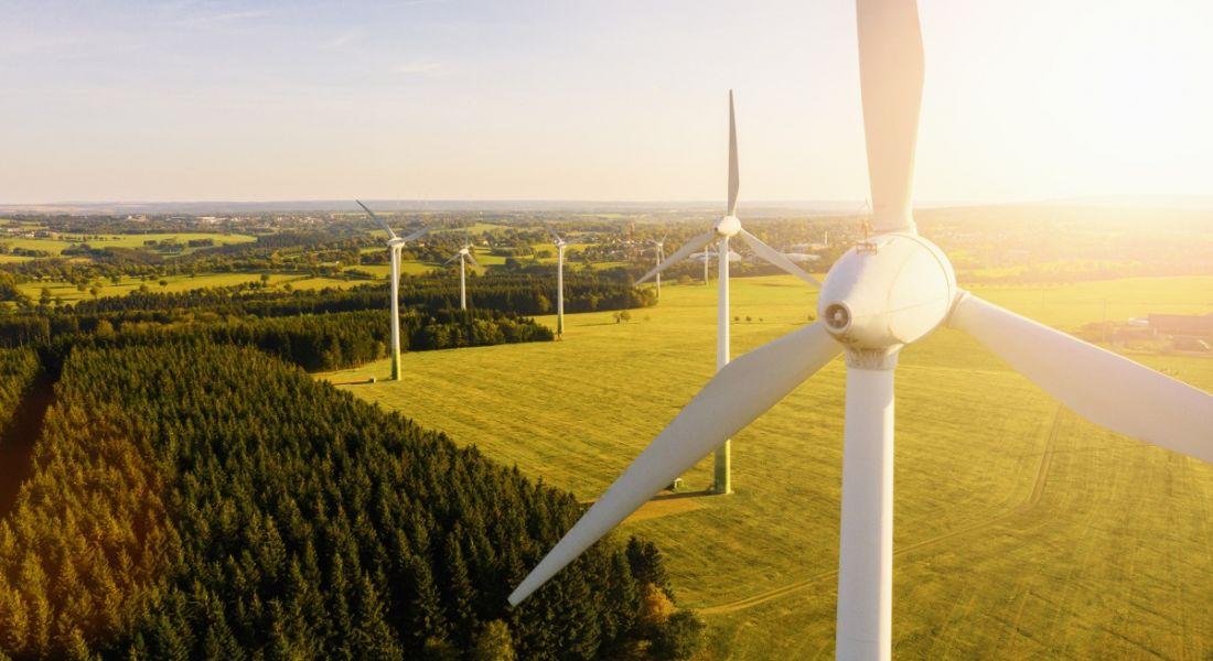 Wind turbines across a green field below a bright blue sky.