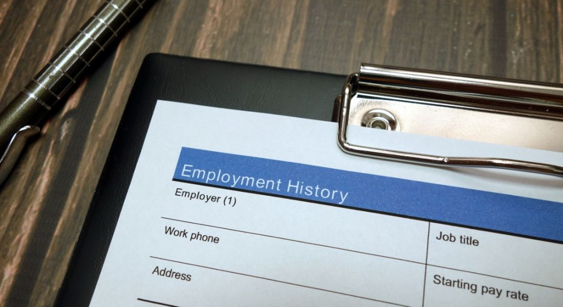 A clipboard is lying on top of a wooden desk with a history of employment form on it.
