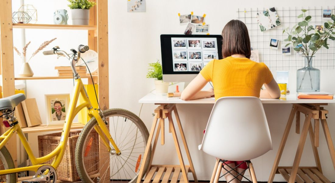 A woman is wearing a yellow top and sitting at her desk doing work, symbolising presenteeism.