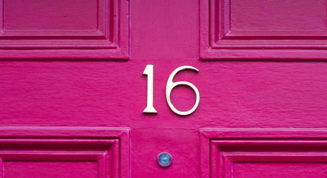The number 16 on a bright pink front door.