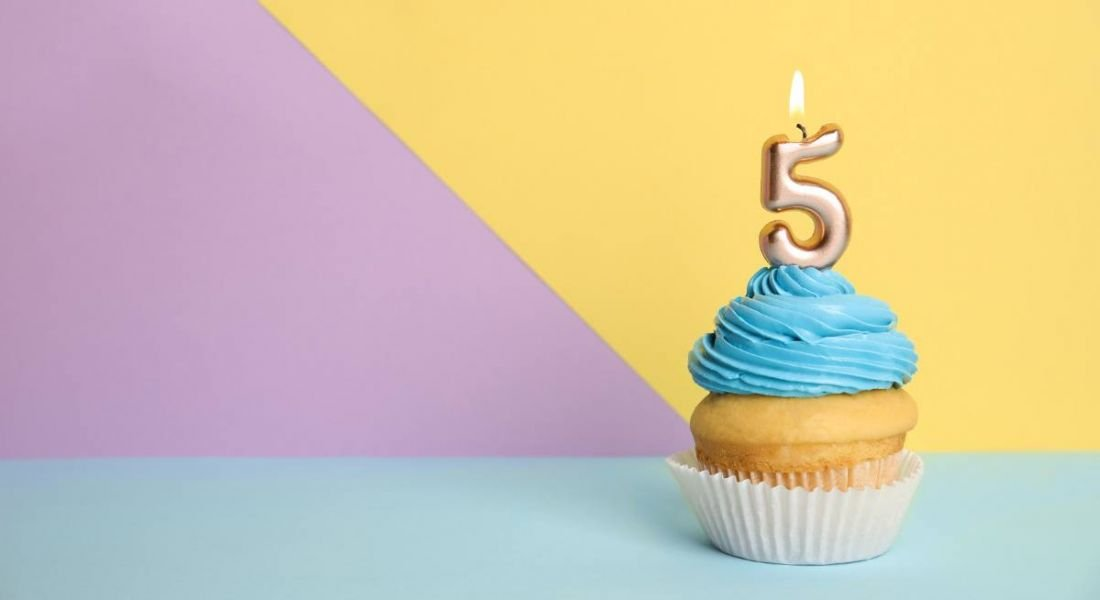 Birthday cupcake with number five candle on colourful background.