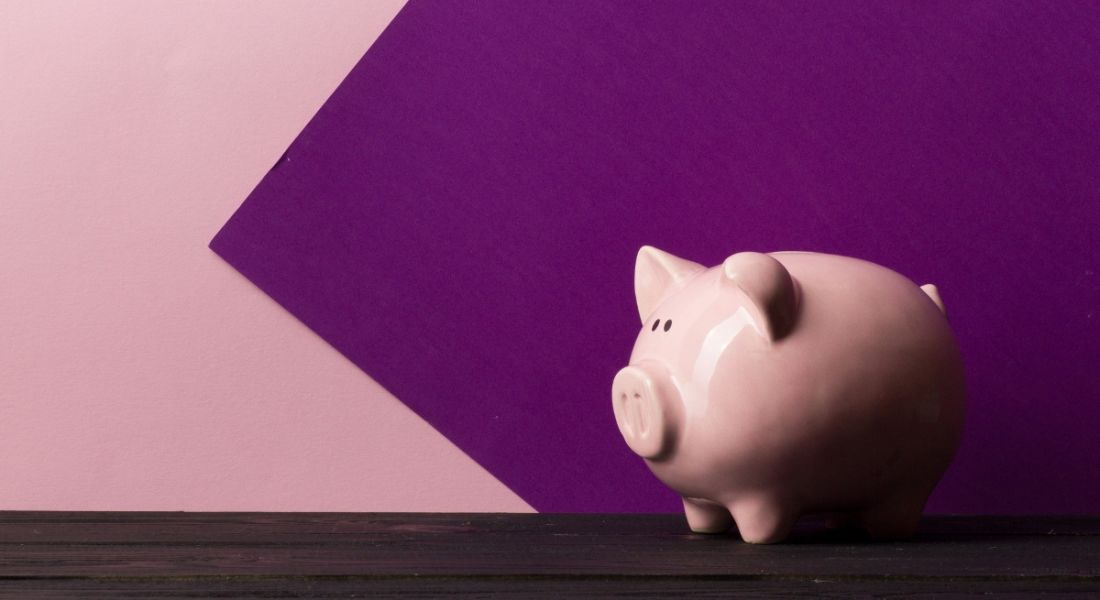 A piggy bank is standing on a dark wooden table against a pink and purple background.