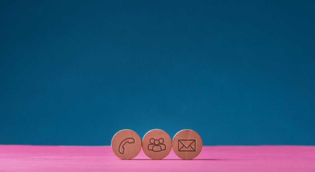 Three wooden cut circles with contact and communication icons on them placed in a row on pink surface over blue background.