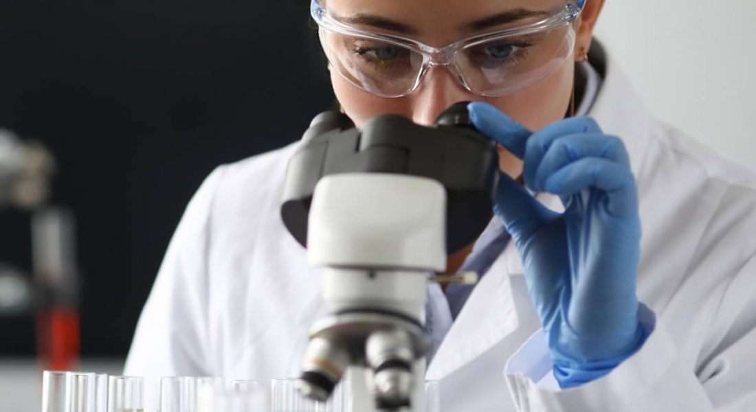 A woman in a white lab coat, wearing blue gloves and goggles, looks into a microscope.