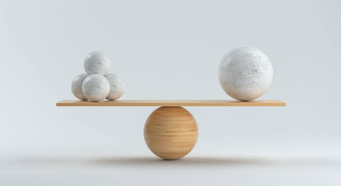A wooden board bearing three stone balls on one side and one large ball on the other is perfectly balance atop a wooden sphere.